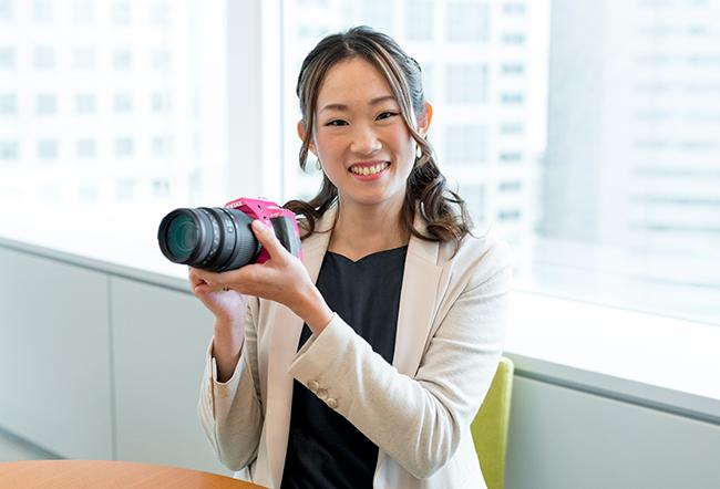取材時に愛用するピンクの一眼レフカメラ(ペンタックス「K50」)を持ってきてもらいました。カメラを構える姿もキマってます!