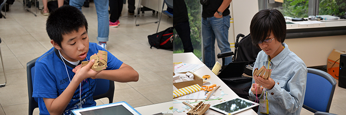 図面を見ながら手のロボットを組み立てる子供たち