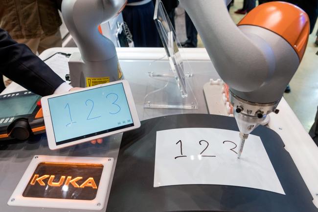 ブースでは「LBR iiwa」がタブレットに書いた文字をロボットが書くデモを展示